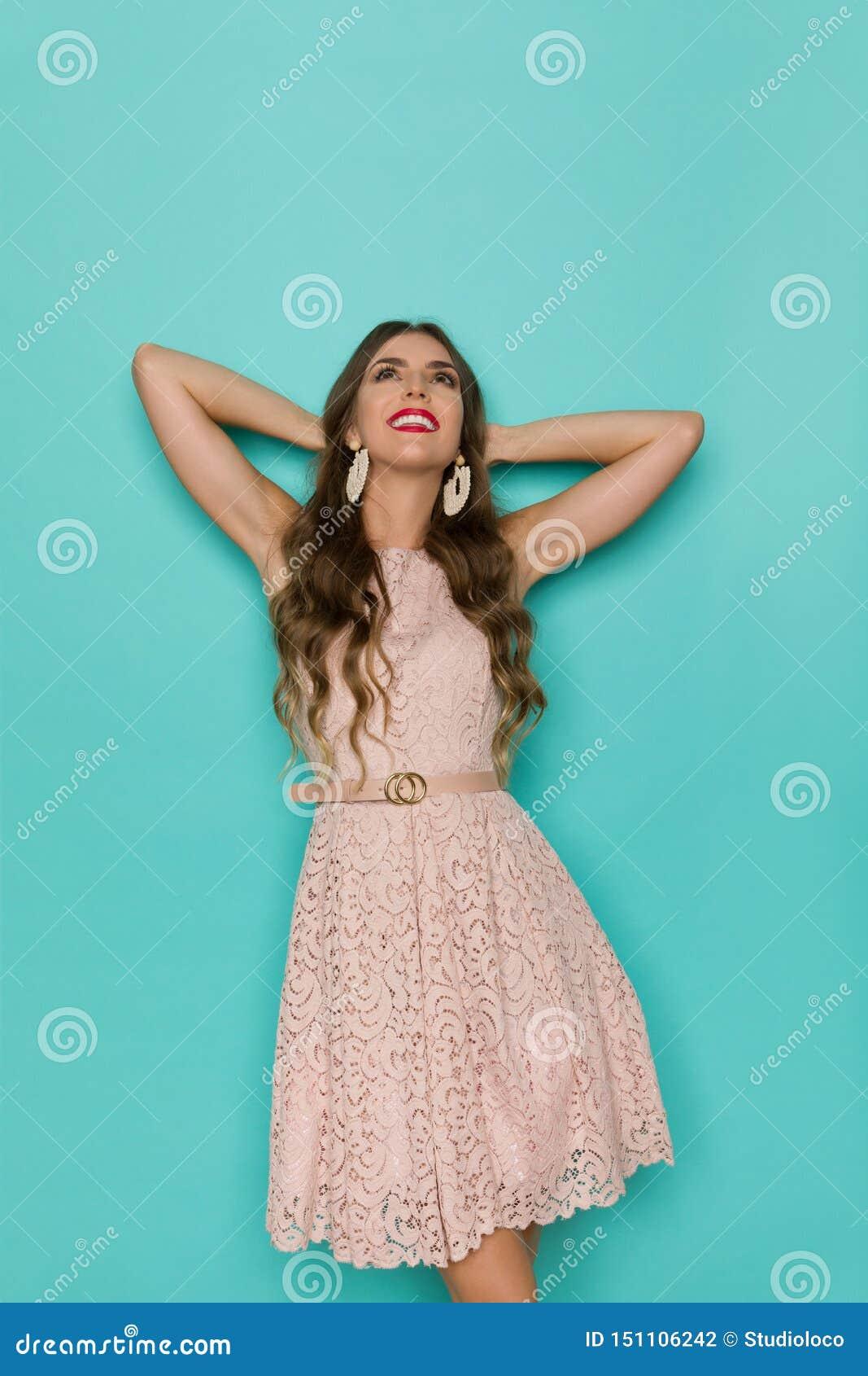 Den kopplade av unga kvinnan i beiga snör åt klänningen ser upp