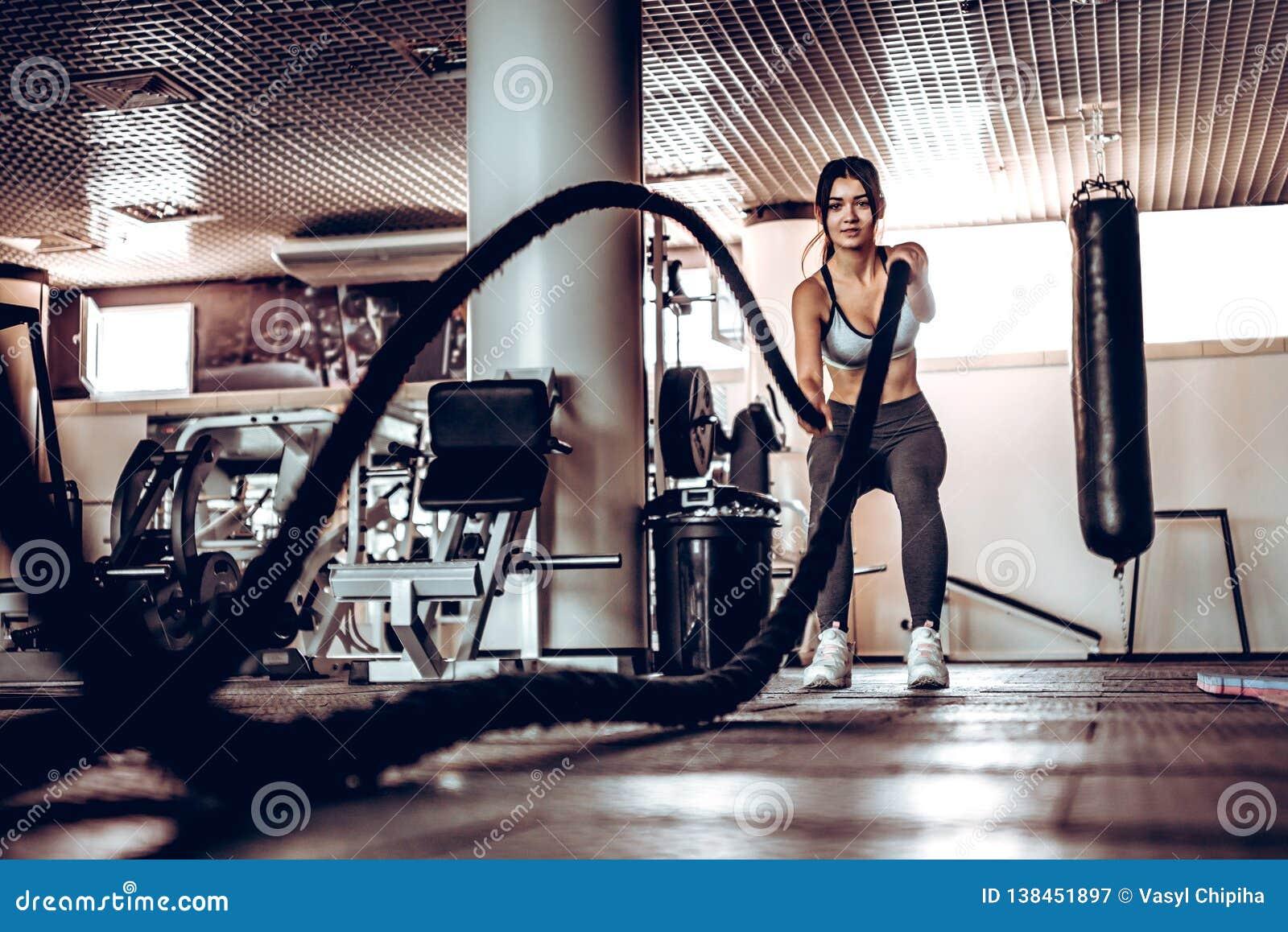 Den kraftiga attraktiva muskulösa kvinnainstruktören gör stridgenomkörare med rep på idrottshallen