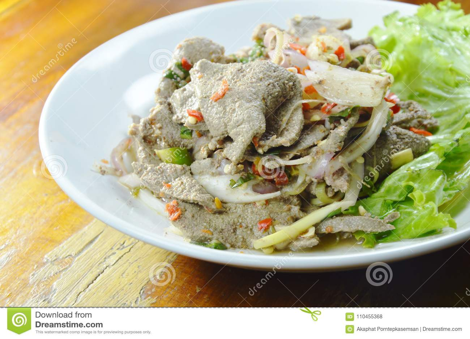 Den kryddiga skivan kokade grisköttleversallad med örten på maträtt