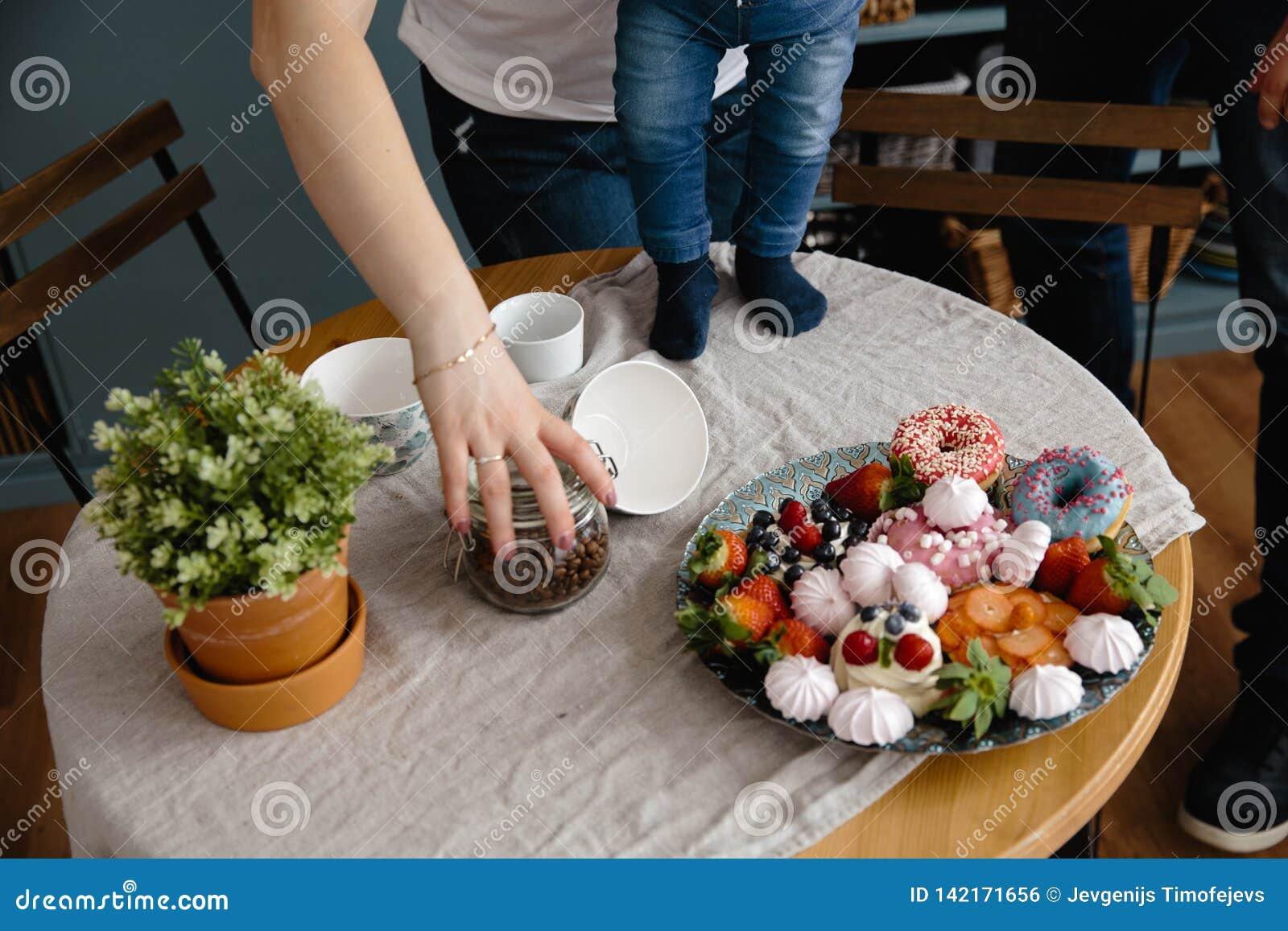 Den kvinnliga handen rymmer kaffebönor och sparar från att falla ner Härlig och färgrik blandning av sefir och frukter på en tabe