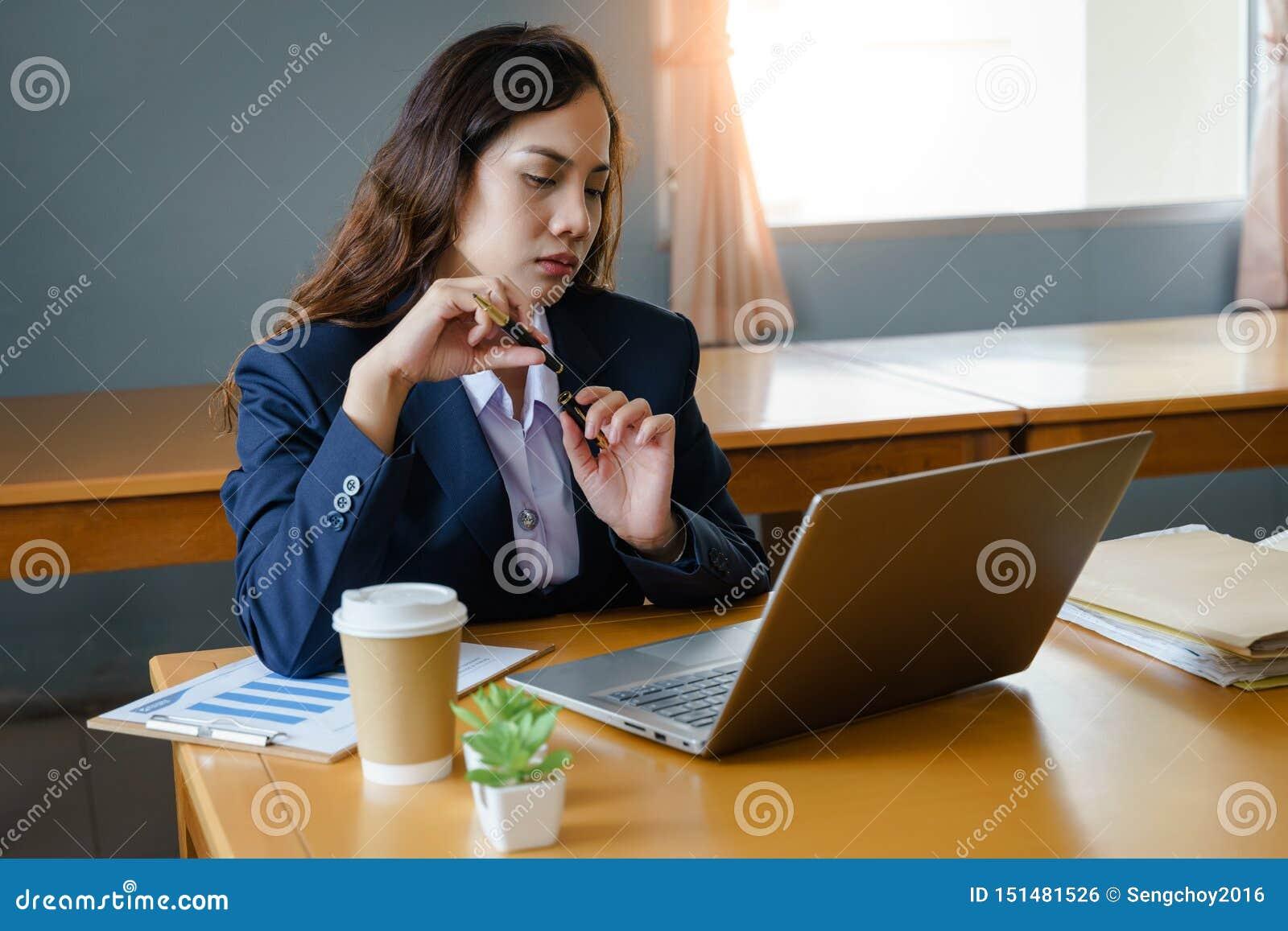Den kvinnliga kontorsarbetaren bär mörkt - den blåa affärsdräkten som arbetar med dokumentmappen och högen av arbetspapper i allv