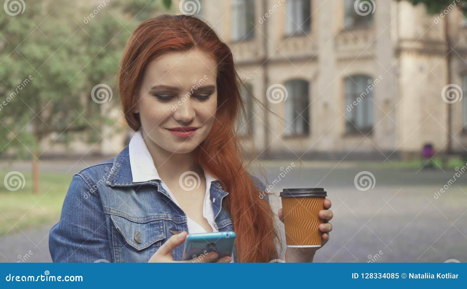 Den kvinnliga studenten dricker kaffe på universitetsområde