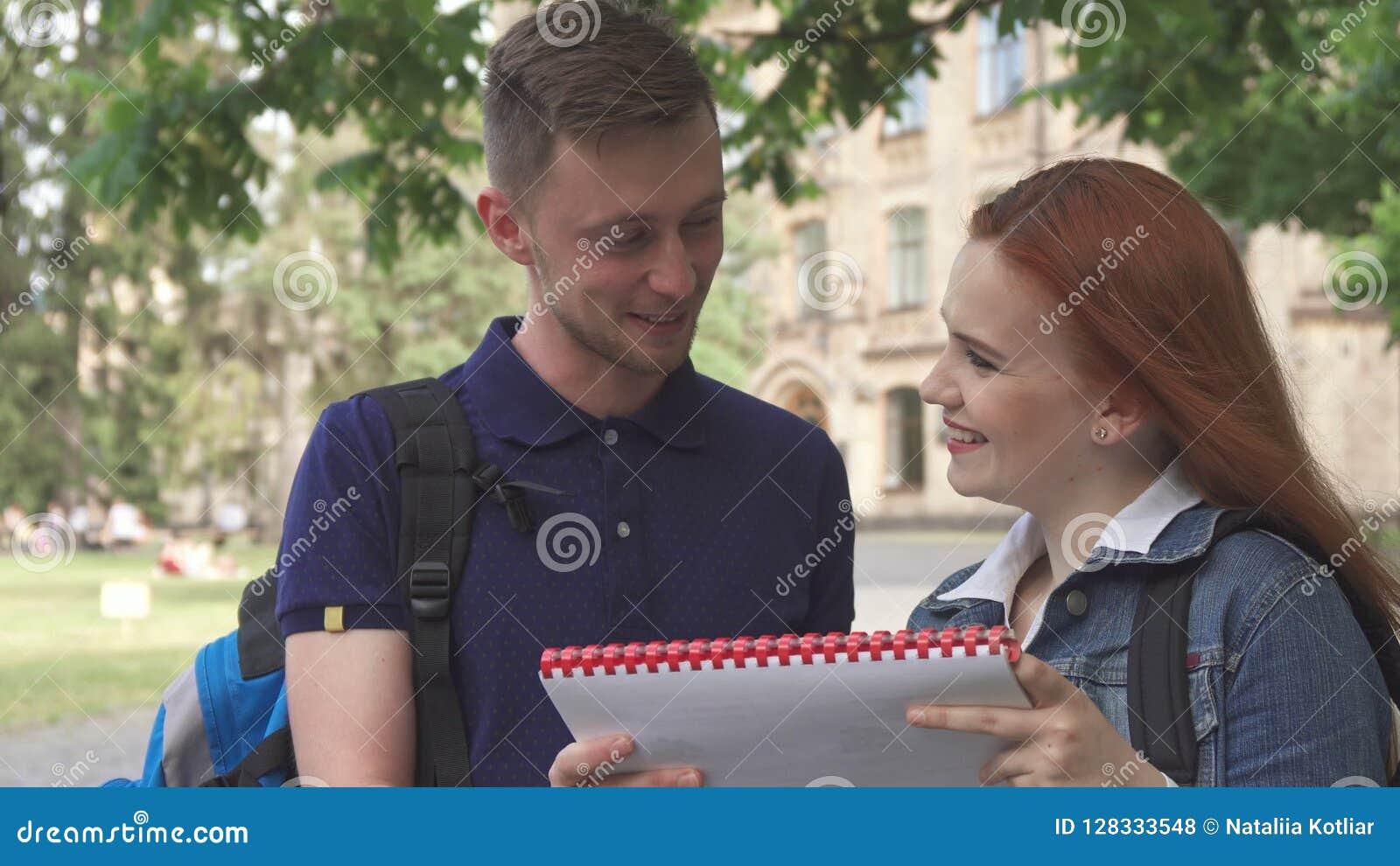 Den kvinnliga studenten frågar hennes klasskompis om något i anteckningsbok på universitetsområde