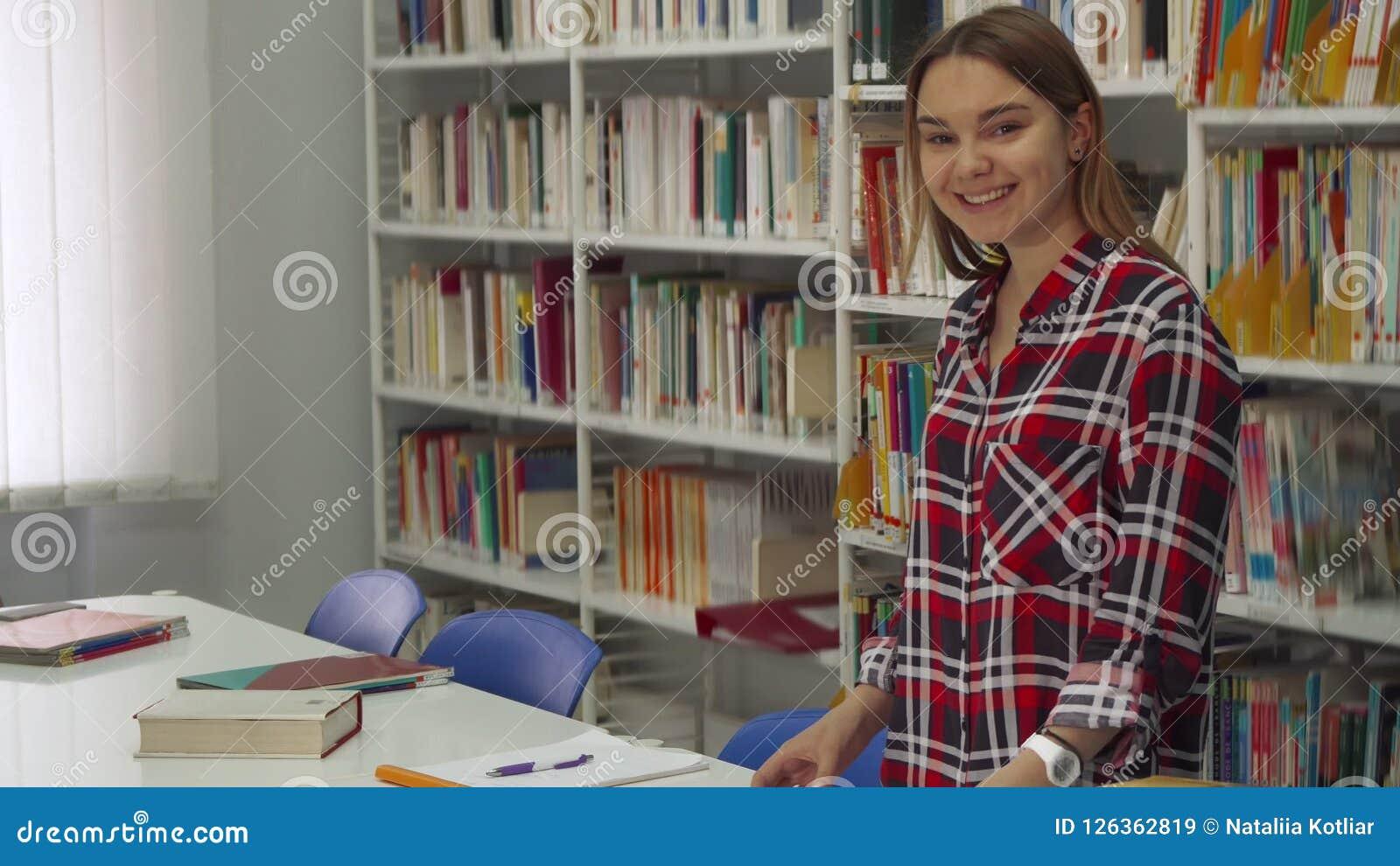 Den kvinnliga studenten poserar på arkivet