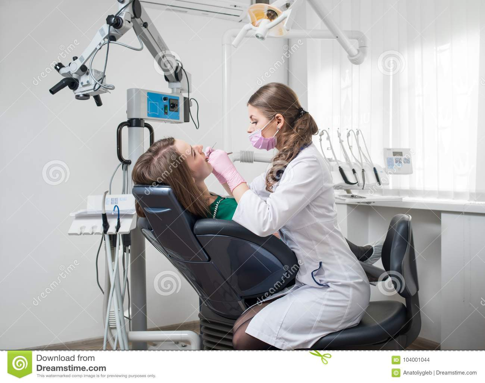Den kvinnliga tandläkaren med tand- hjälpmedel - avspegla och sondera behandling av tålmodiga tänder på det tand- klinikkontoret