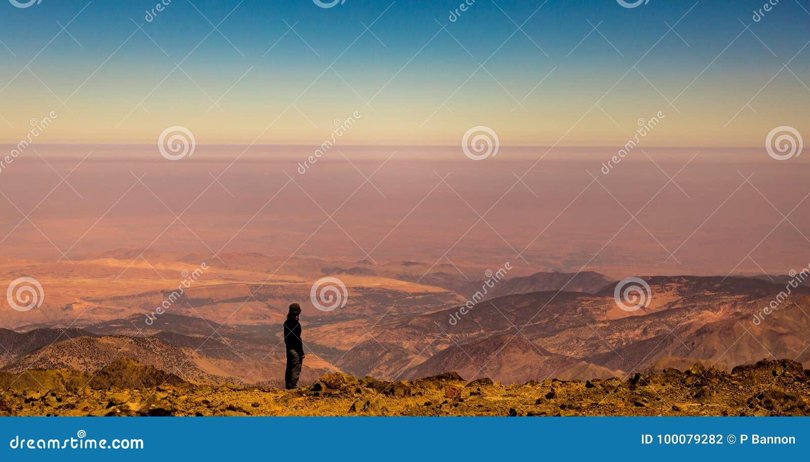 Den kvinnliga trekkeren tycker om sikten från toppmötet av Jbel Toubkal, kartbokberg, Marocko