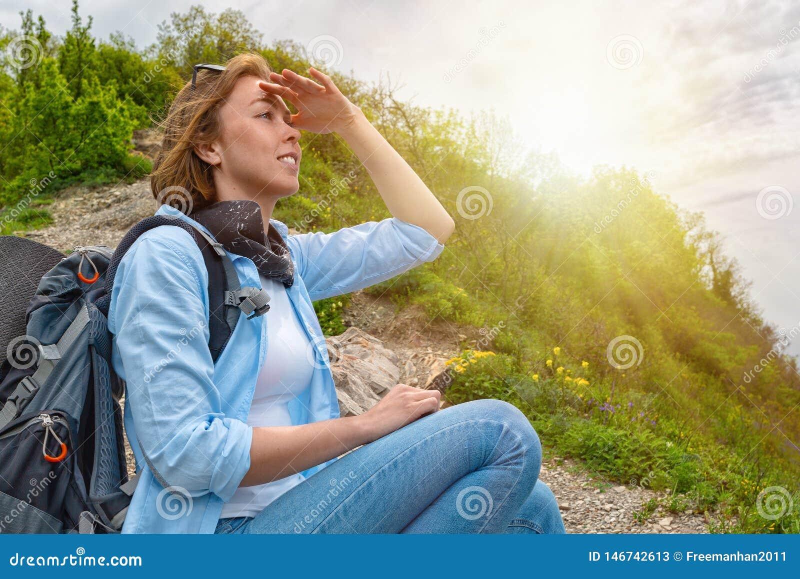 Den kvinnliga turisten satt ner för att vila överst av berget och blickarna in i avståndet close upp ljus sun