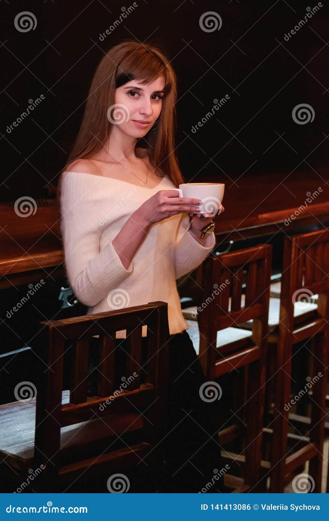 Den långhåriga härliga flickan i en vit tröja står i en coffee shop på en trätabell med en kopp, en ensam flicka