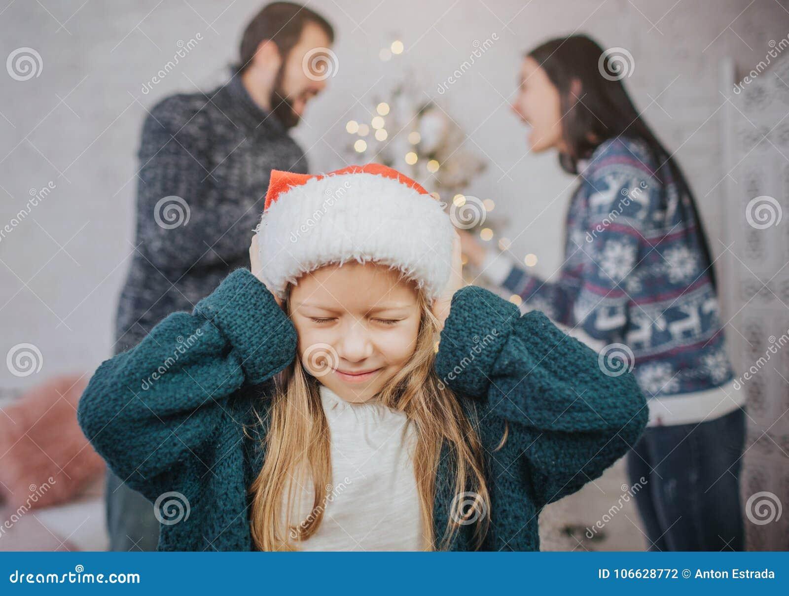 Den ledsna desperata lilla flickan under föräldrar grälar Stoppa till öronen Familjen grälar på helgdagsaftonen av jul