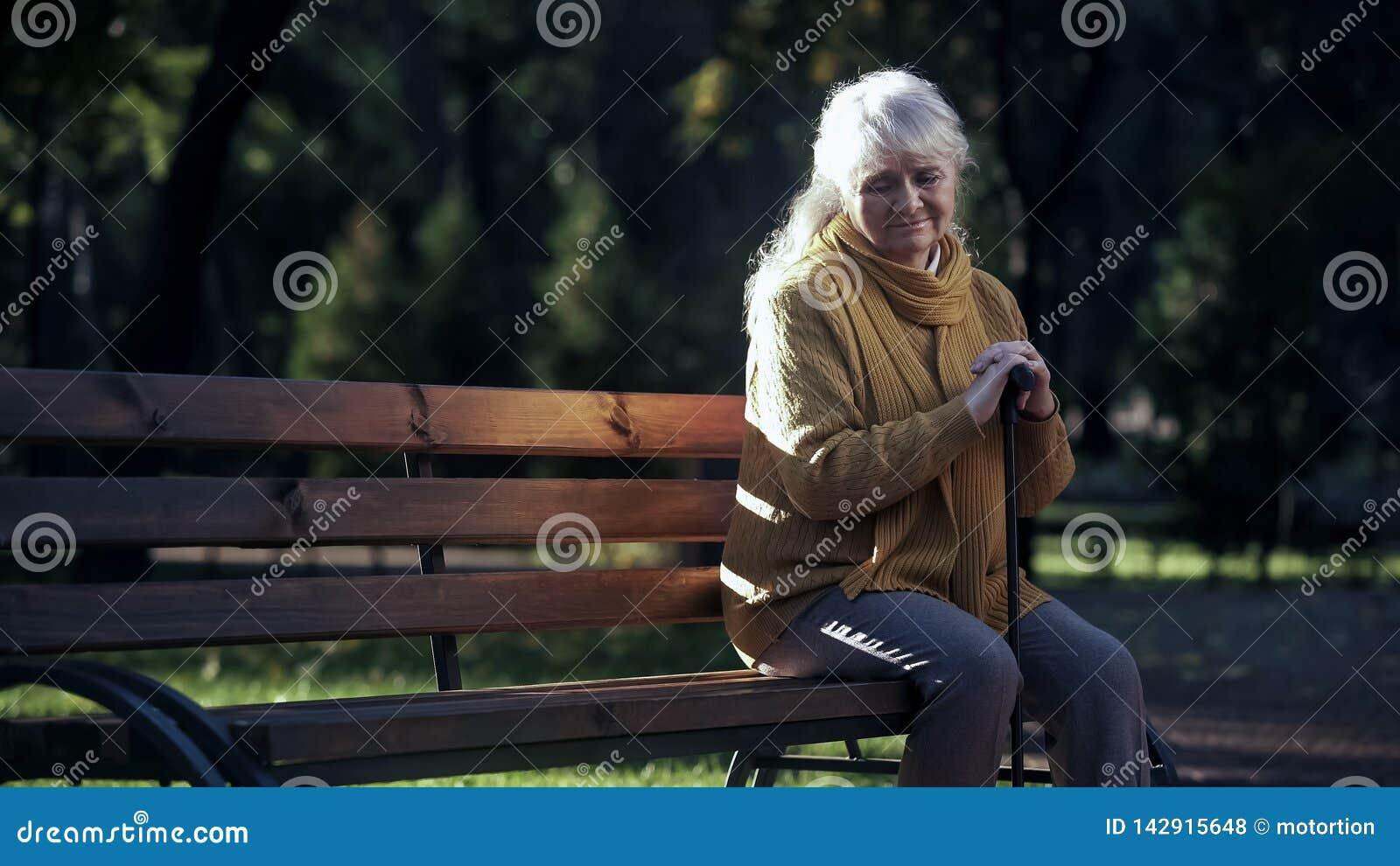 Den ledsna ensamma gamla kvinnan som sitter på bänk parkerar in, övergett äldre folk bara