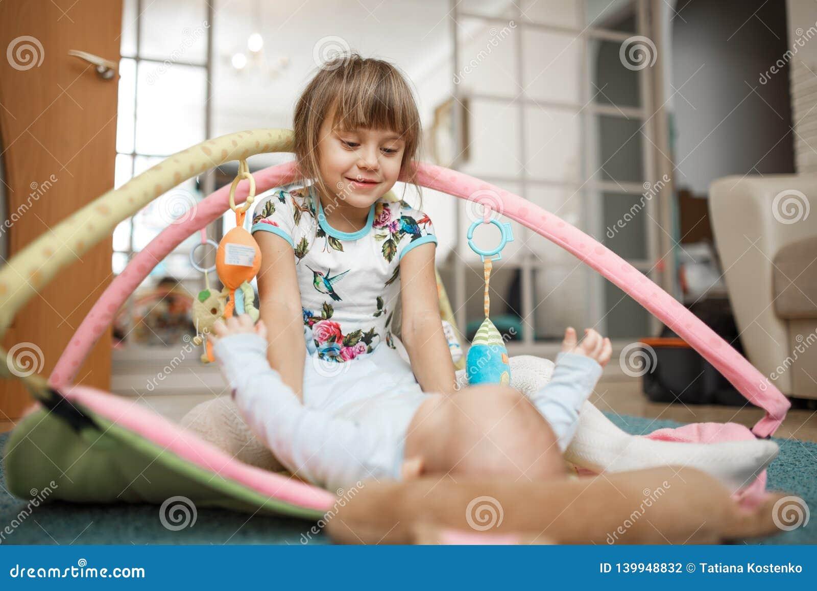 Den lilla charmiga flickan ser hennes mycket lilla broder som ligger på mattan på golvet i rummet