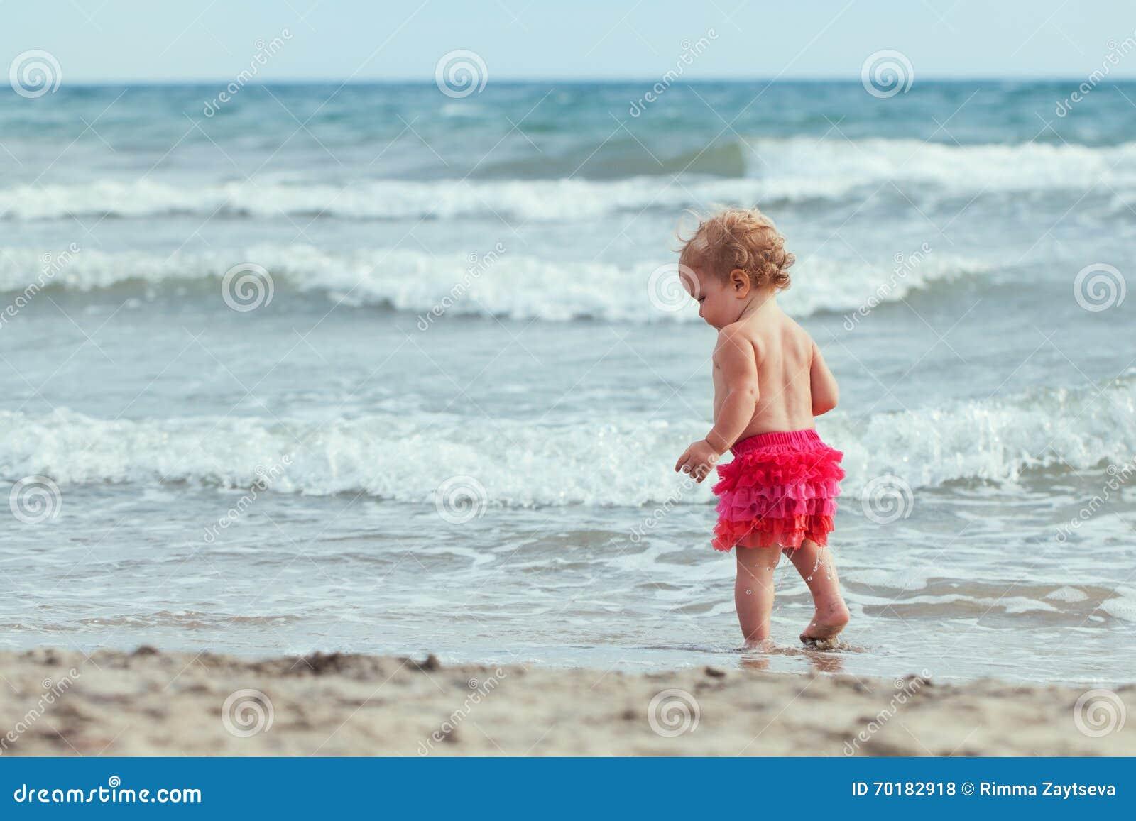 Den lilla gulliga lyckliga flickan badar i havet, Italien som är utomhus-