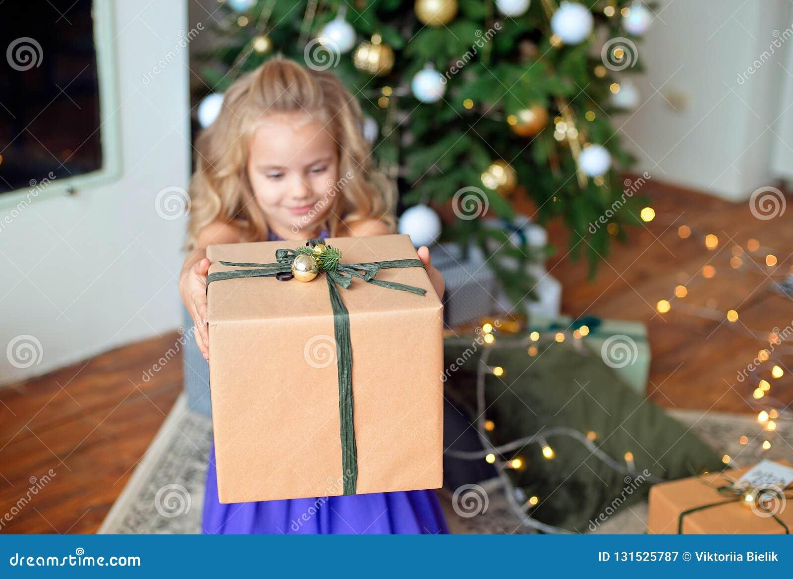 Den lilla härliga flickan med blont lockigt hår sträcker en julgåva mot bakgrunden av julgranen