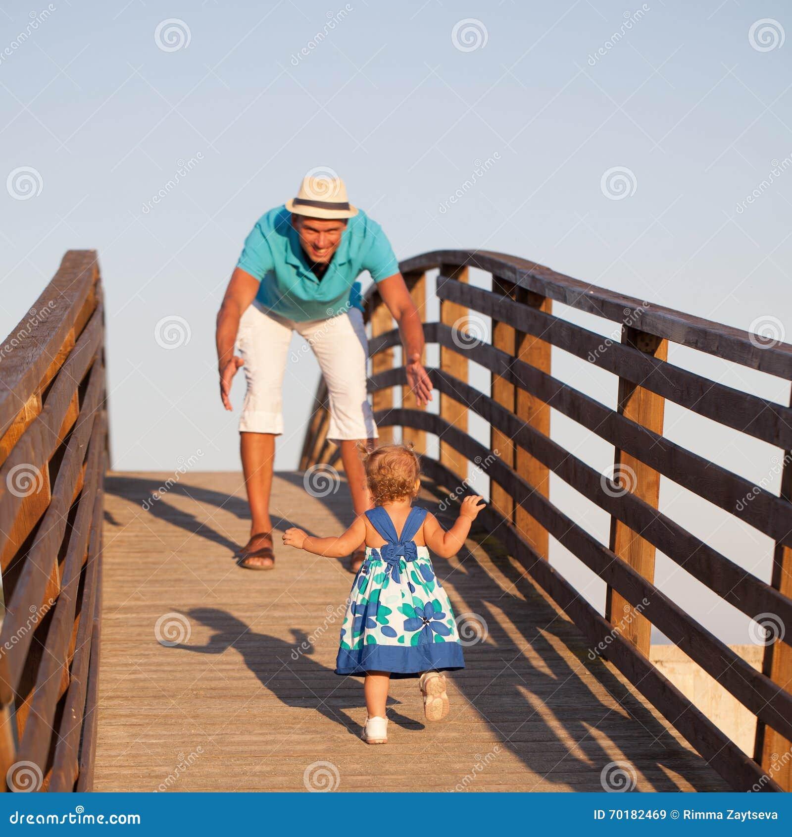 Den lilla härliga nätta flickan går på träbron till hans fader