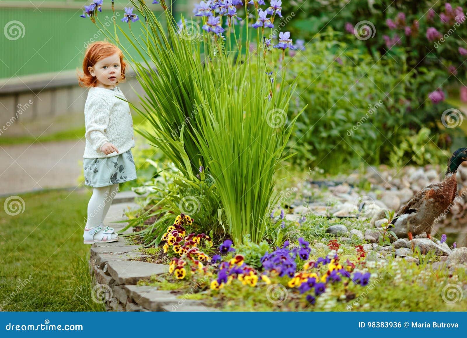 Den lilla härliga rödhåriga flickan behandla som ett barn flickaställningar nära ett damm in