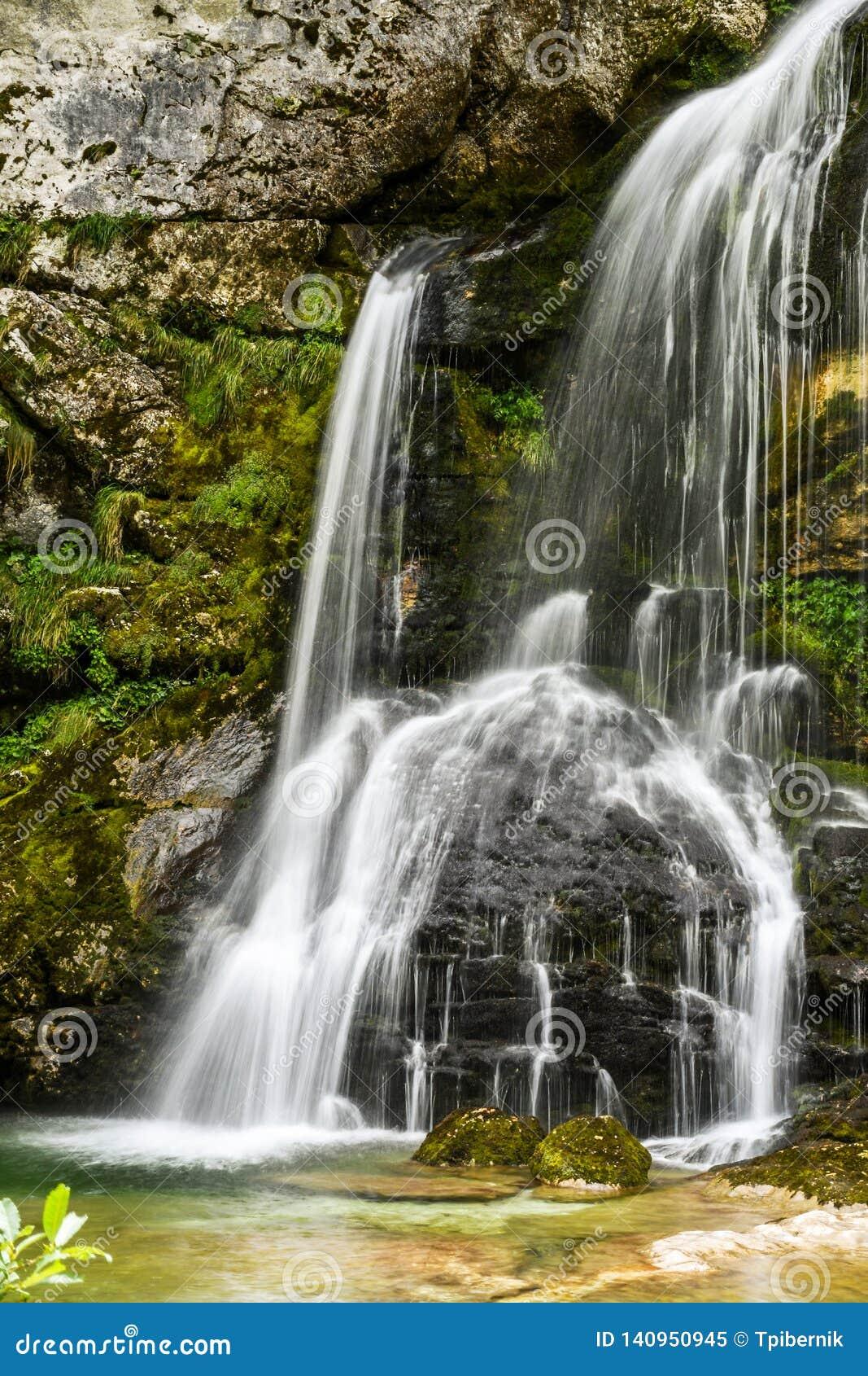 Den lilla härliga vattenfallet som faller över grå färger, vaggar