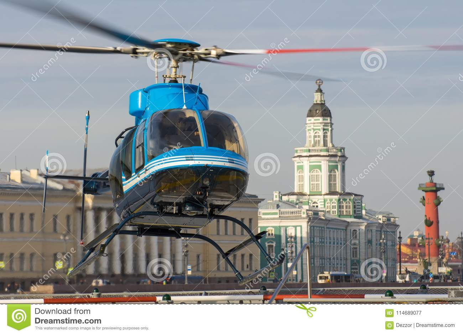 Den lilla helikoptern tar av från helipaden i St Petersburg, mot bakgrunden av Kunstkameraen, pilen av Vasilyen