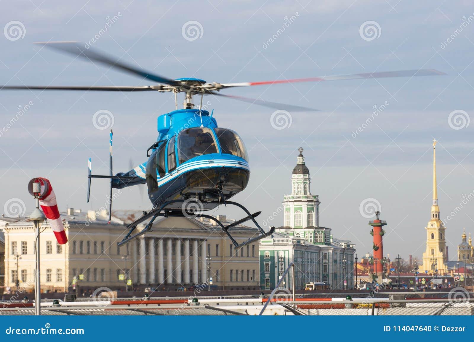 Den lilla helikoptern tar av från helipaden i St Petersburg, mot bakgrunden av Kunstkameraen, pilen av Vasilyevsen