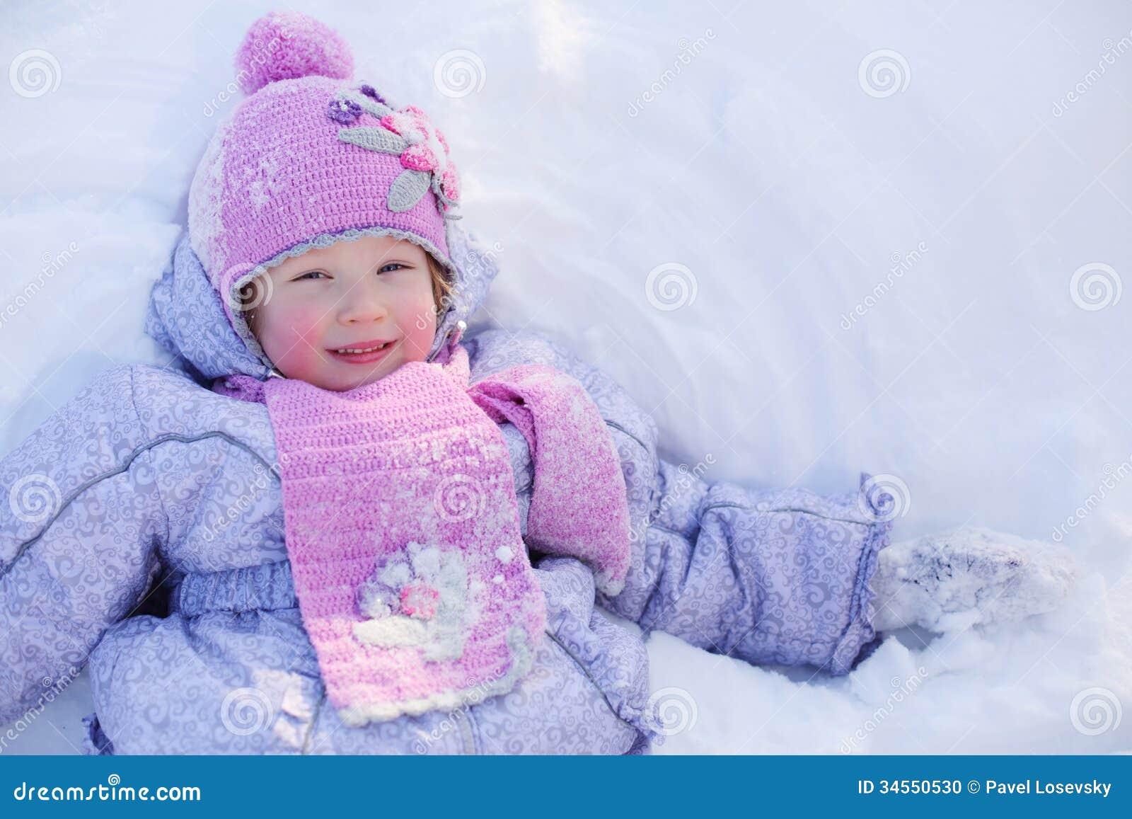 Den lilla le flickan i halsduk och hatt ligger på snö på vintern