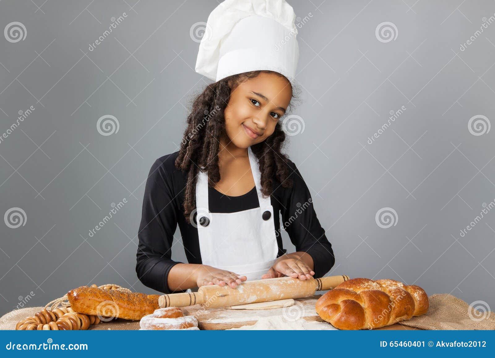 Den lilla mörkhyade flickan rullar degen Barnet lär att laga mat Kläd- och kockhatt