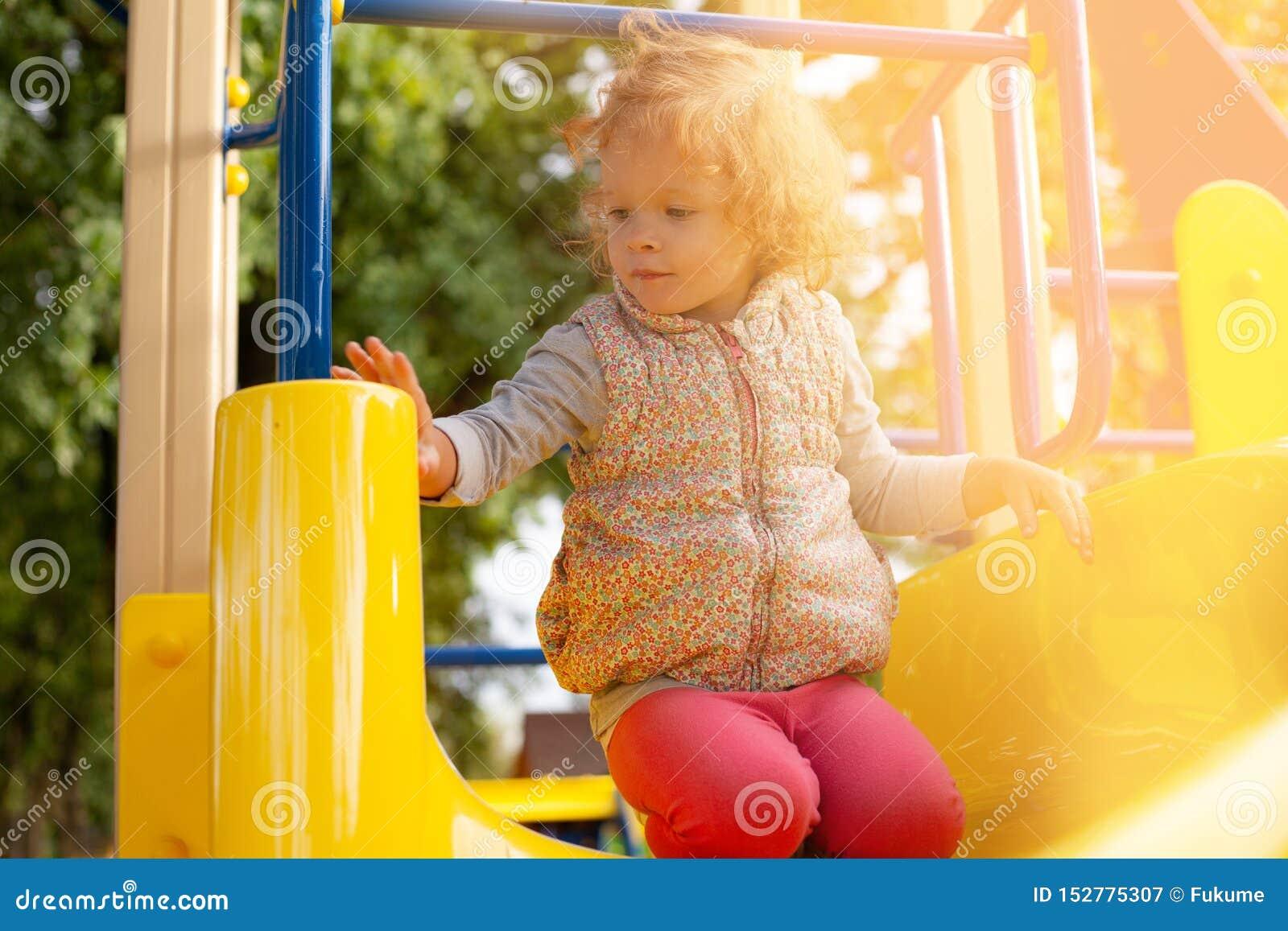 Den lilla rödhåriga flickan sitter på en kulle i barn parkerar och värma sig i det varma solskenet