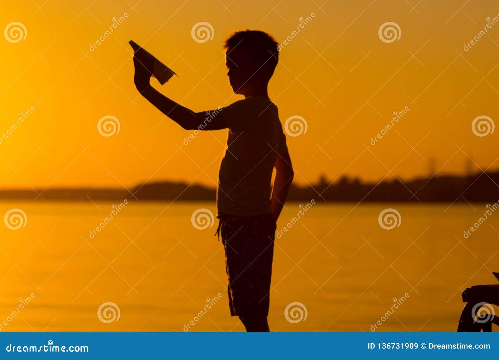 Den lilla ungen rymmer origami av det pappers- flygplanet i hans hand och lekar på solnedgången på bakgrunden av sjön Passionates
