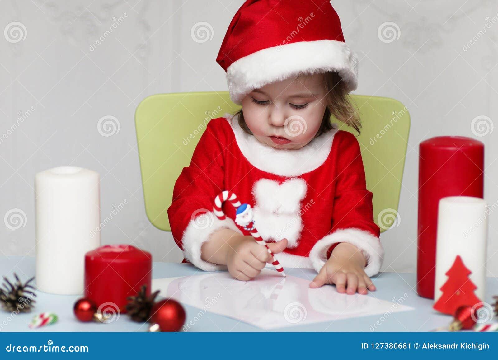 Den lilla ungen skrivar brevet till jultomten