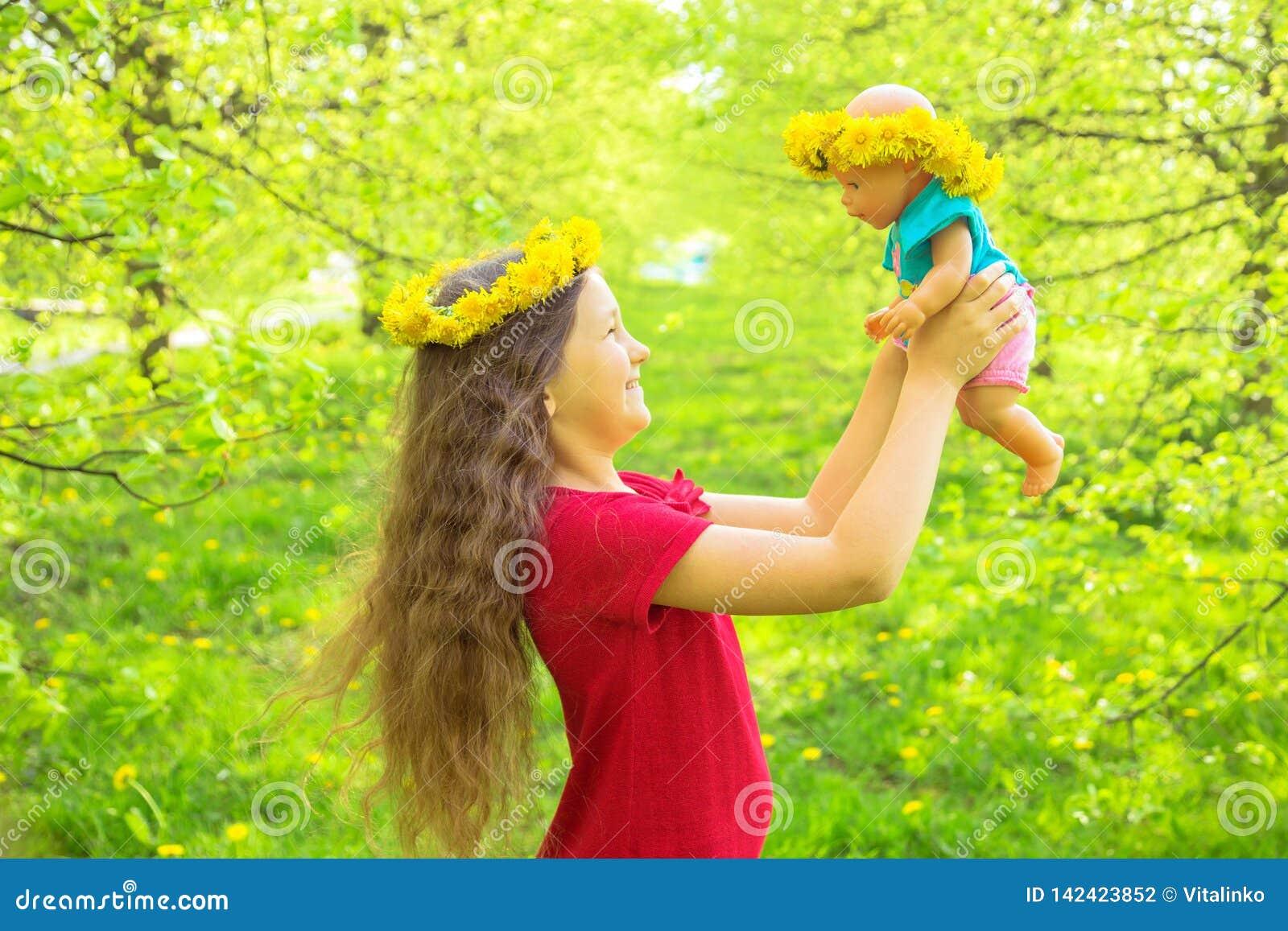 Den lilla ungen spelar med en docka lycklig din feriesommar för familj