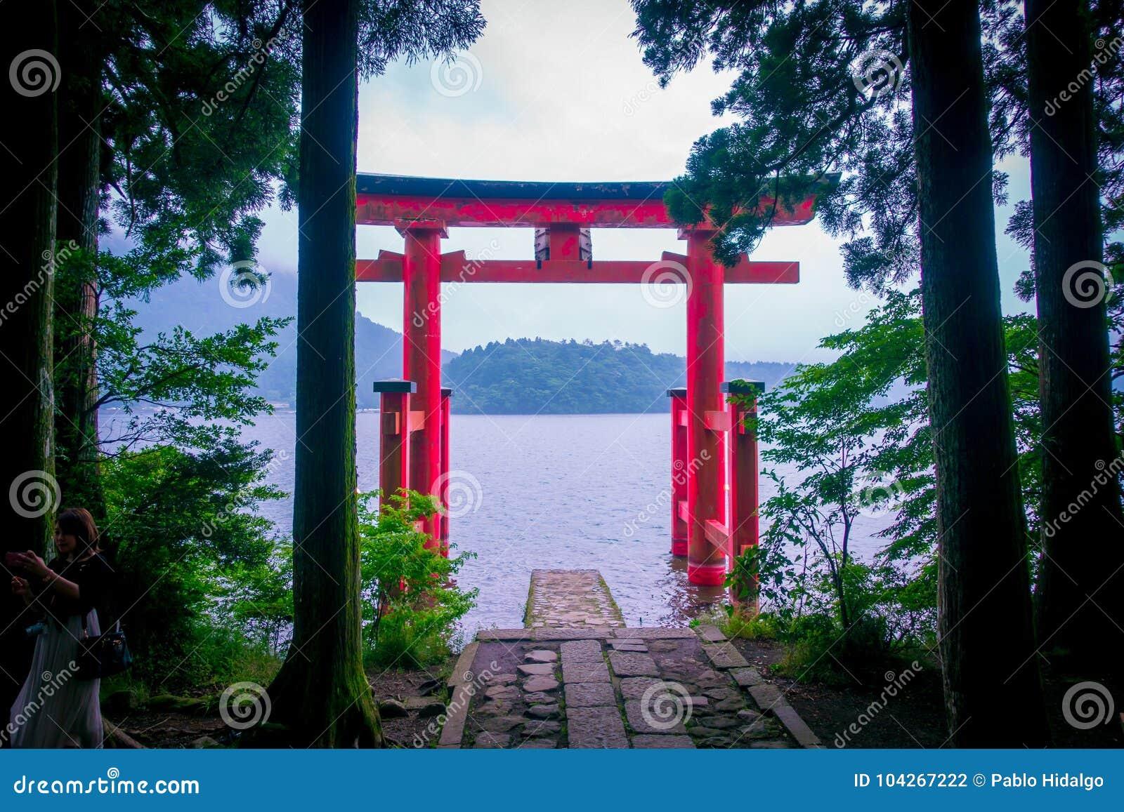 Den ljusa röda Torii porten doppade i vattnet av Ashi sjön, caldera med berg på bakgrunden Hakone relikskrin