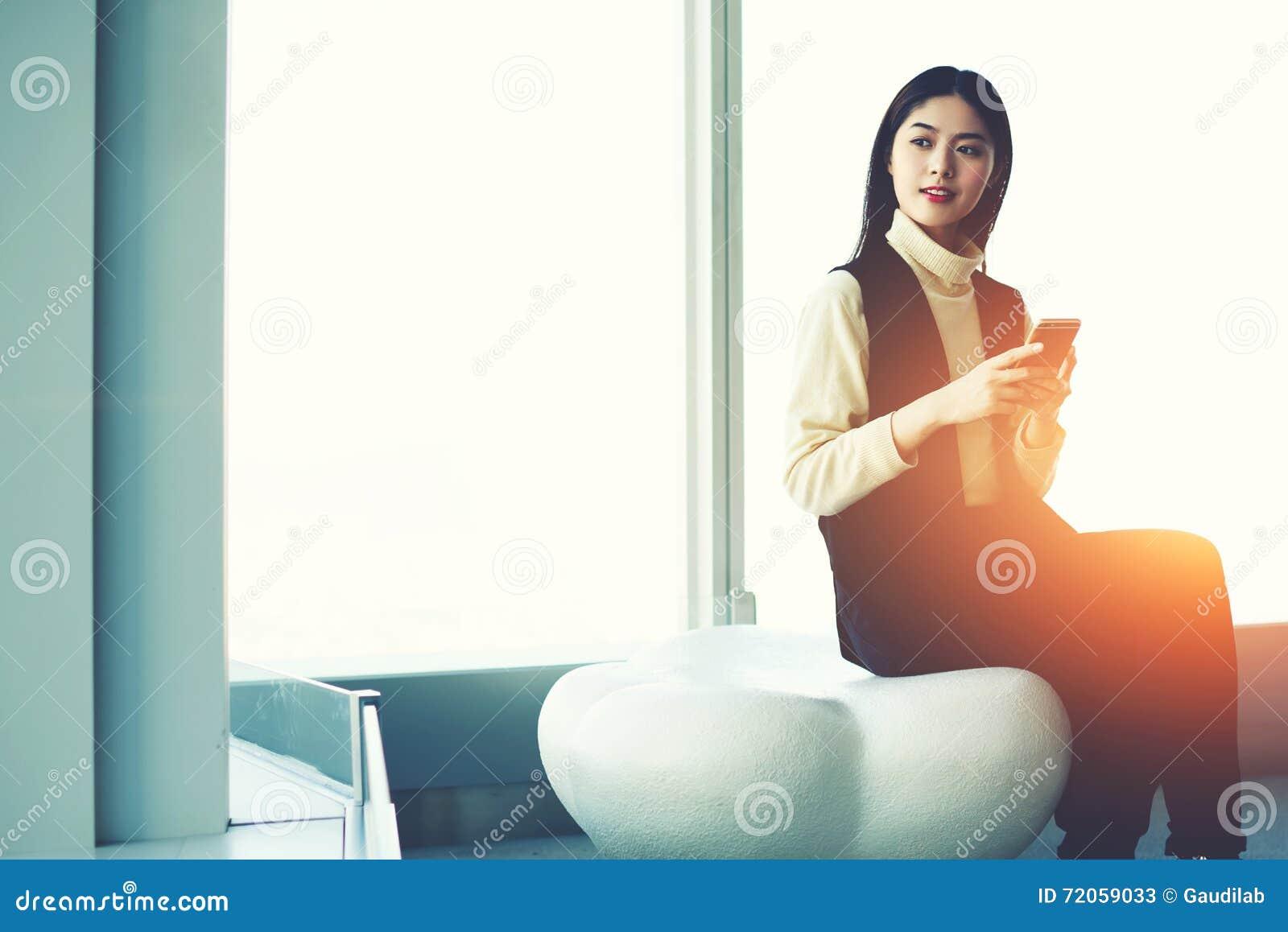 Den lyckade asiatiska affärskvinnan knyter kontakt via apparaten för celltelefonen