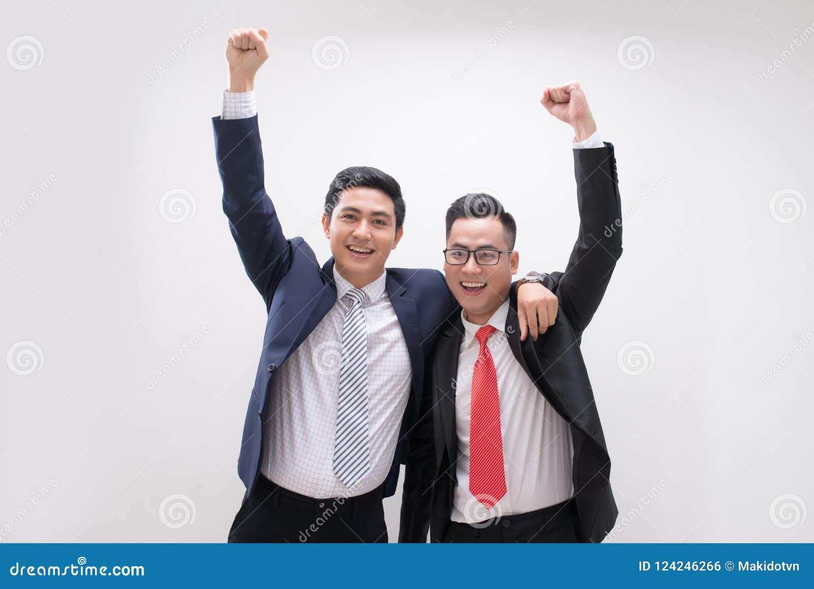 Den lyckade asiatiska affärsmannen räcker upp mening lycklig eller seger med