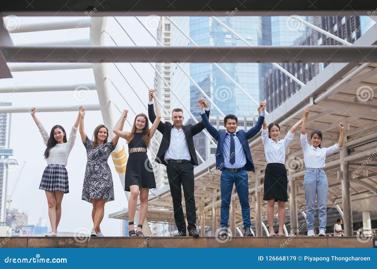 Den lyckade gruppen av affärsfolk, framgångprestationhand lyftte, lagarbete för att uppnå mål
