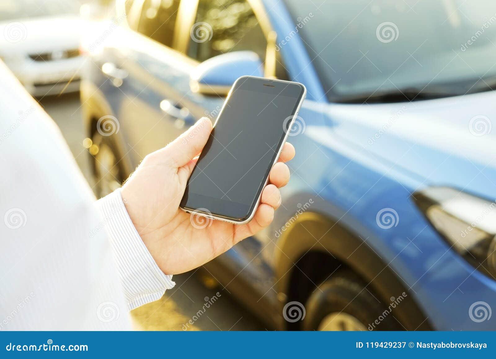 Den lyckade lyckliga unga mannen och hans bil i mjuk solnedgång tänder på urbanistic bakgrund Affärsman med medlet på vägrenen