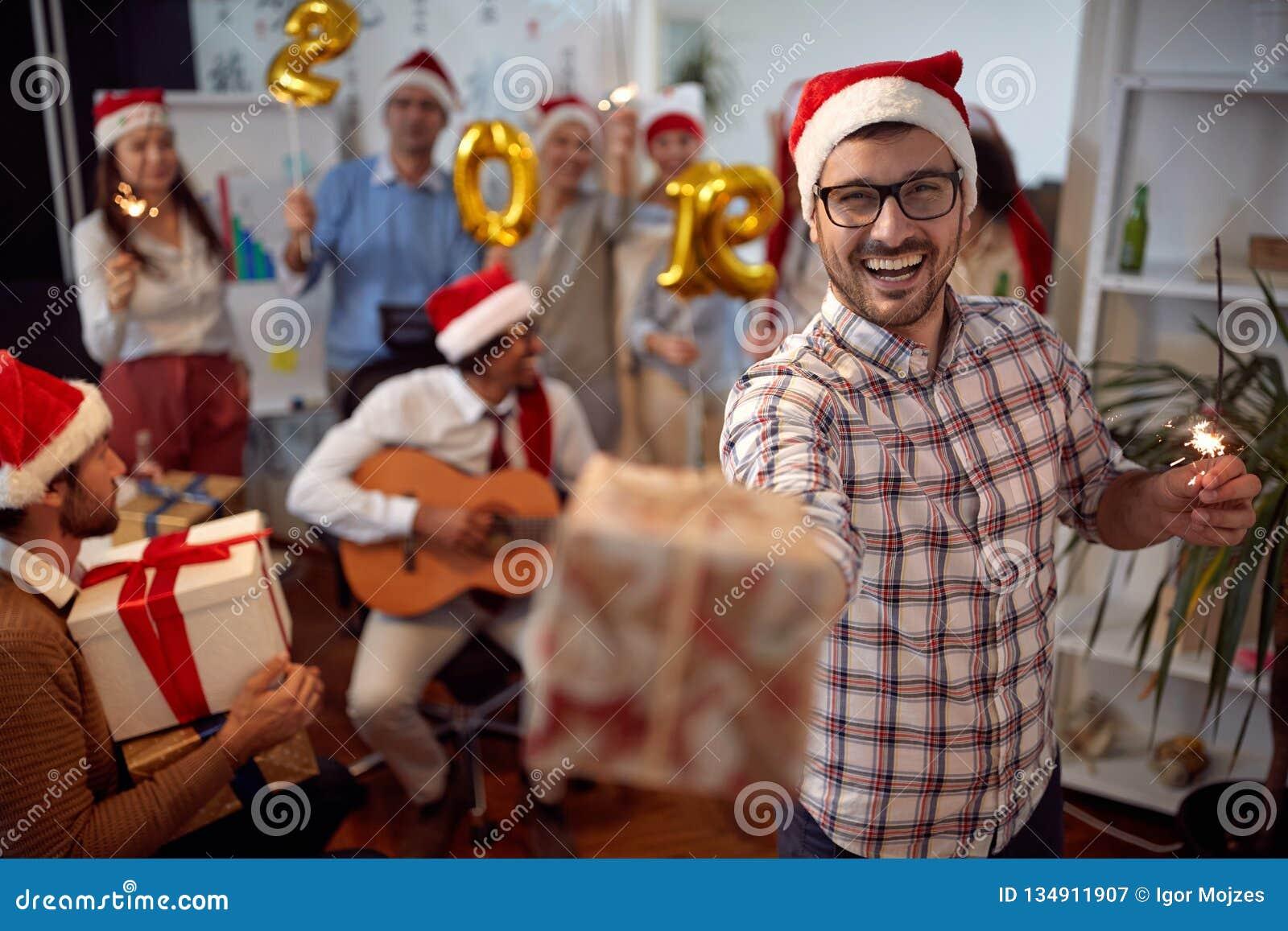 Den lyckliga affärsmannen har gyckel i jultomtenhatt- och utbytesgåvor på Xmas-partiet med hans kollegor