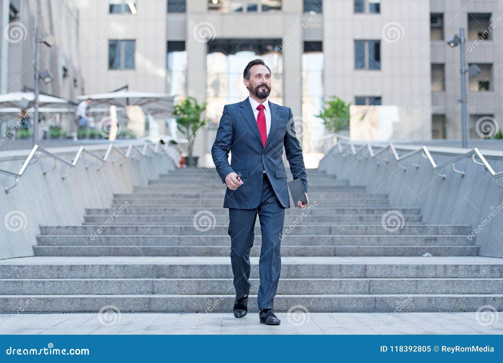 Den lyckliga affärspersonen går bottenvåning i brådskarörelse med minnestavlan Ung modern affärsman som går i finansmitt
