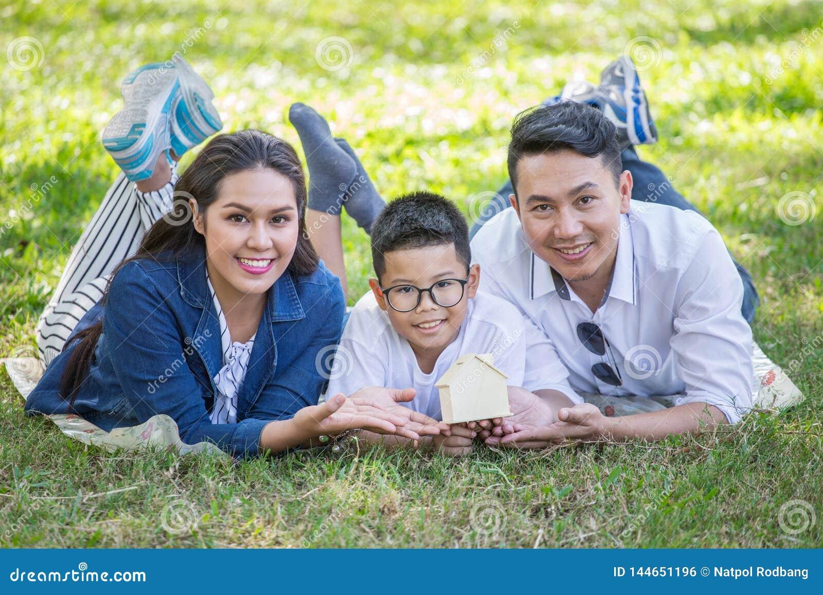 Den lyckliga asiatiska familjen, föräldrar och deras barn som ner ligger på gräs parkerar in, att se kameran tillsammans Fadern f