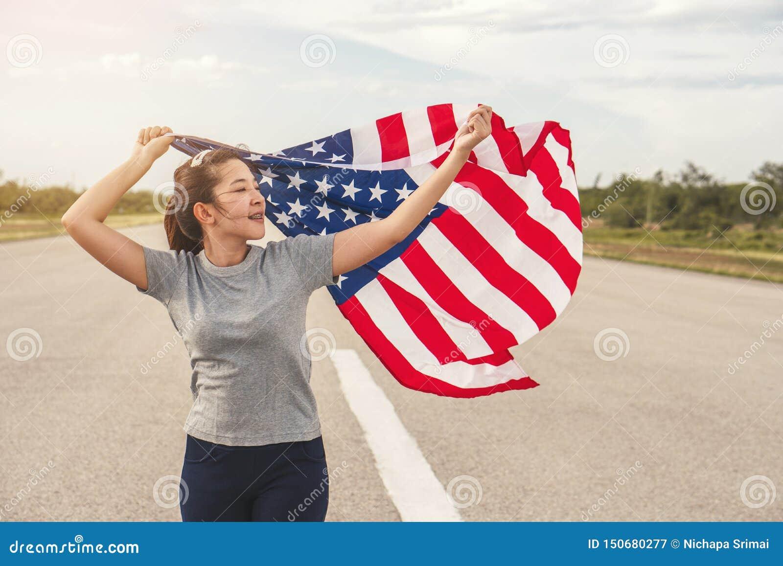 Den lyckliga asiatiska kvinnan med amerikanska flaggan USA firar 4th Juli