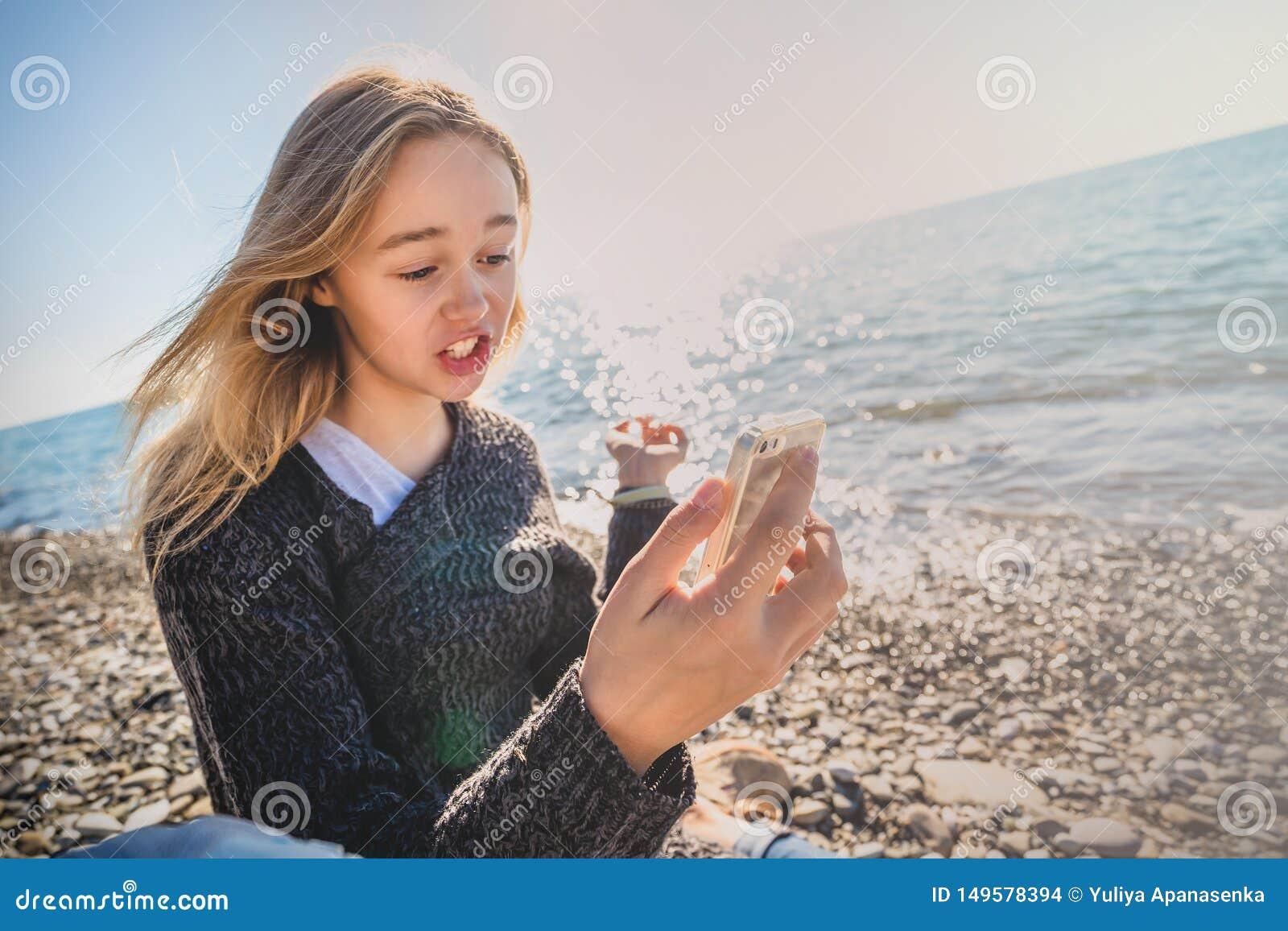 Den lyckliga avkopplade unga kvinnan som mediterar i en yoga, poserar på stranden