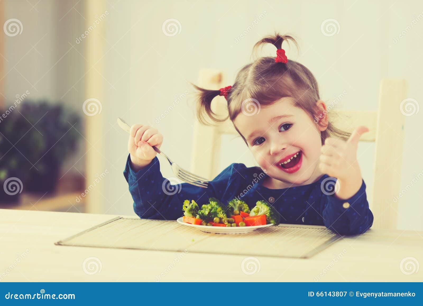 Den lyckliga barnflickan äter upp grönsaker och visningtummar