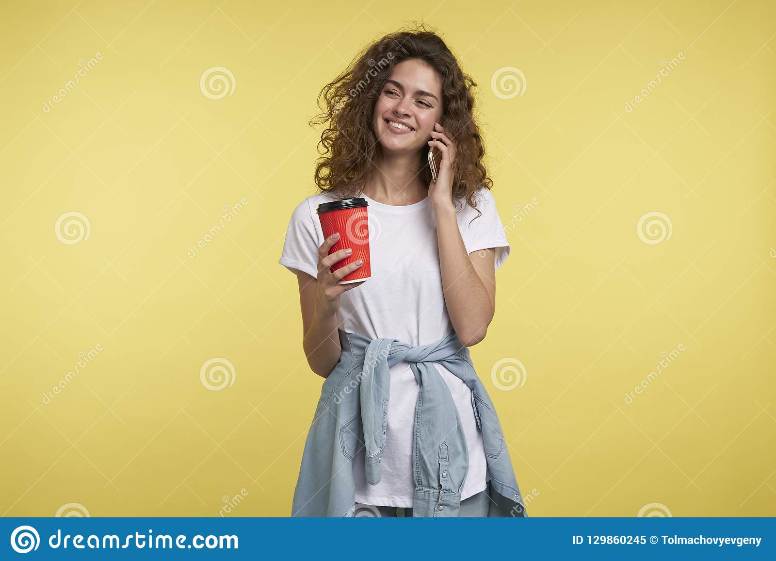 Den lyckliga brunettkvinnan med lockigt hår talar, genom telefonen och att rymma kaffekoppen i handen som isoleras