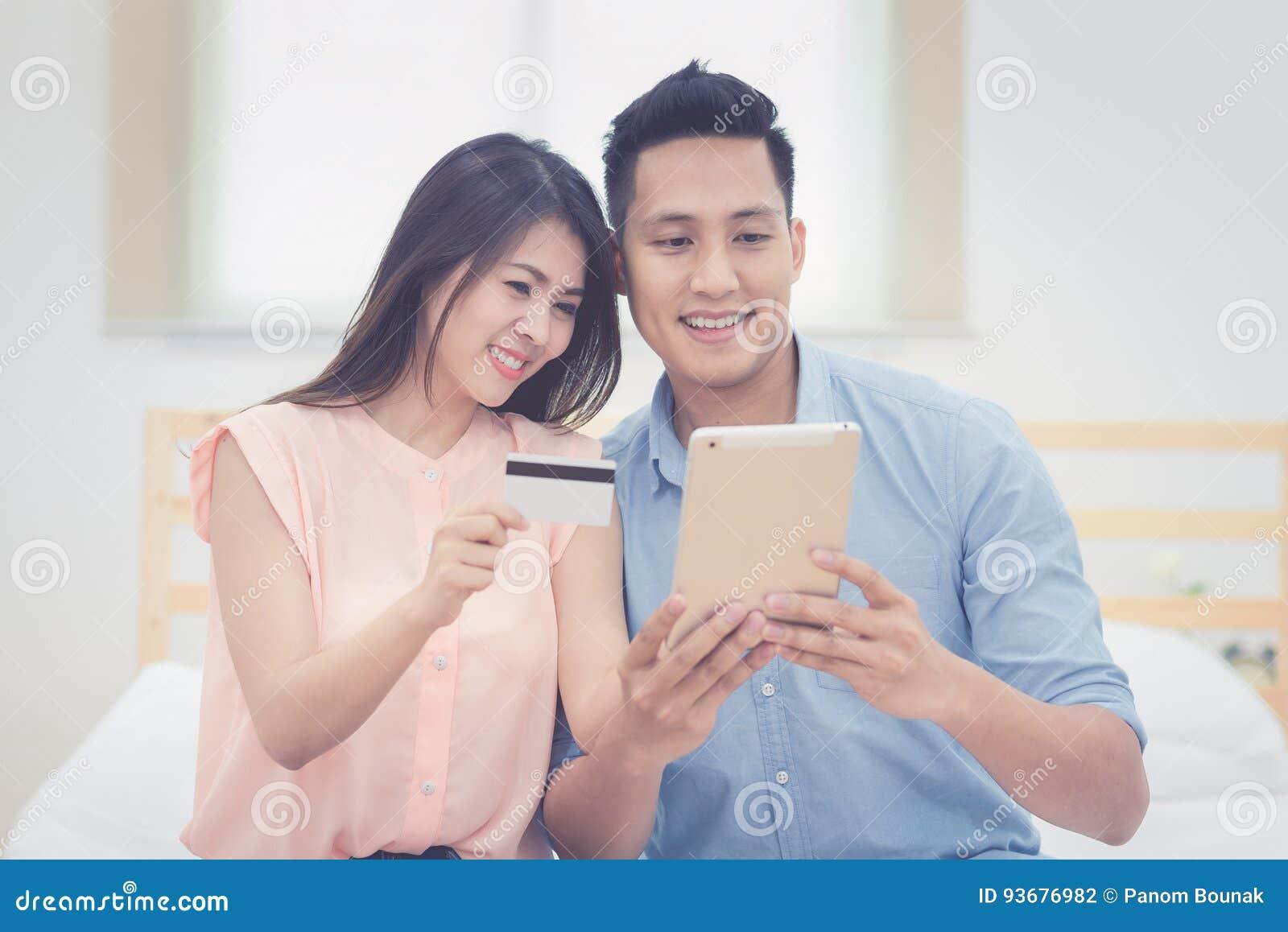 Den lyckliga familjen, asiatiska parvänner tycker om att använda den smarta minnestavlan