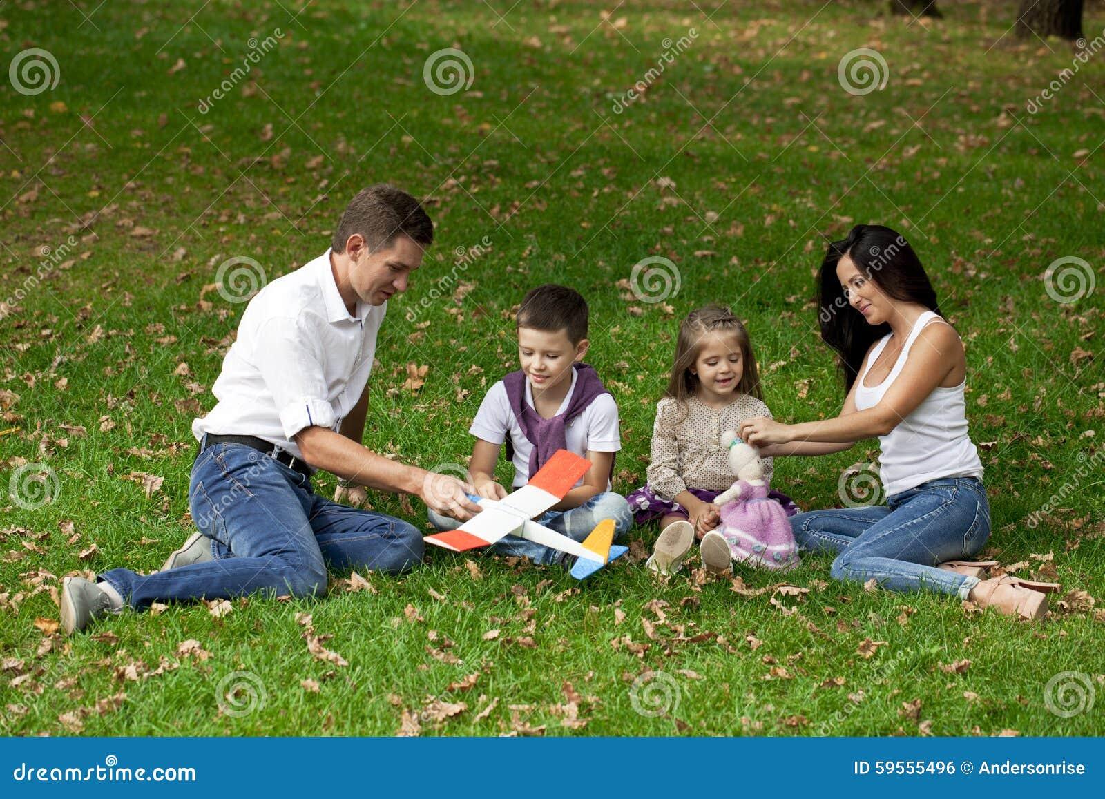 Den lyckliga familjen av fyra som vilar i hösten, parkerar