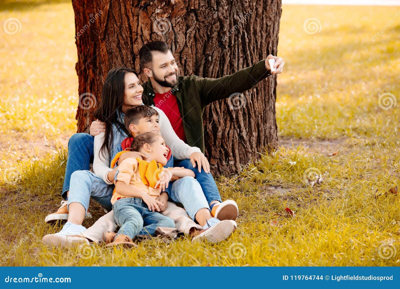 Den lyckliga familjen med två barn som tillsammans sitter på gräs parkerar in, och tar en selfie