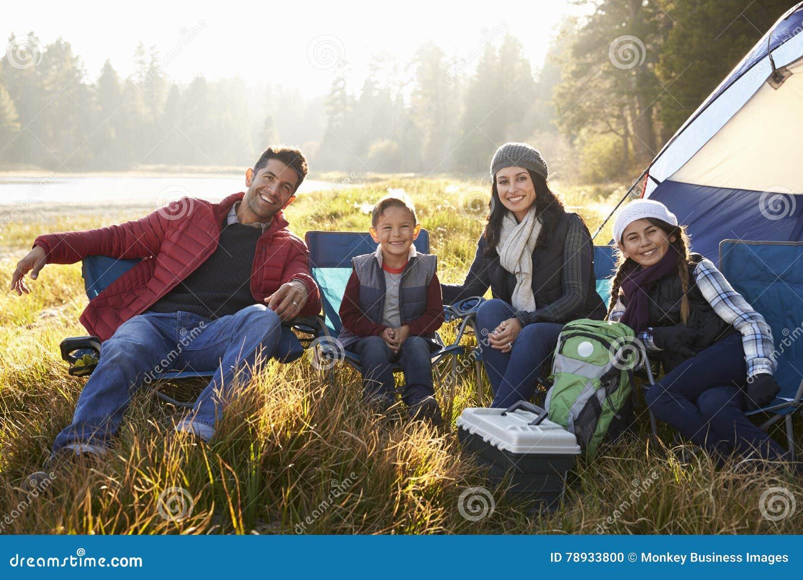 Den lyckliga familjen på en campa tur sitter av tältet som ser till kameran