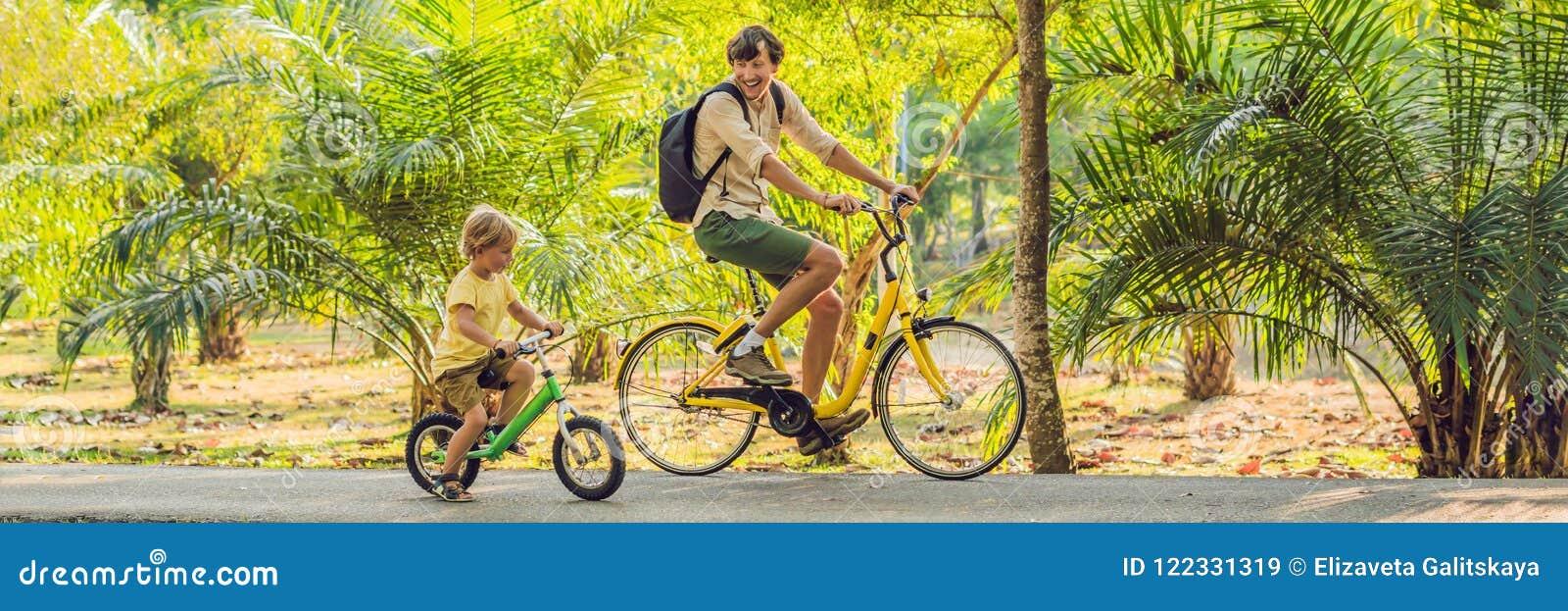 Den lyckliga familjen rider cyklar utomhus och att le Avla på en cykel och en son på ett balancebikeBANER, långt format