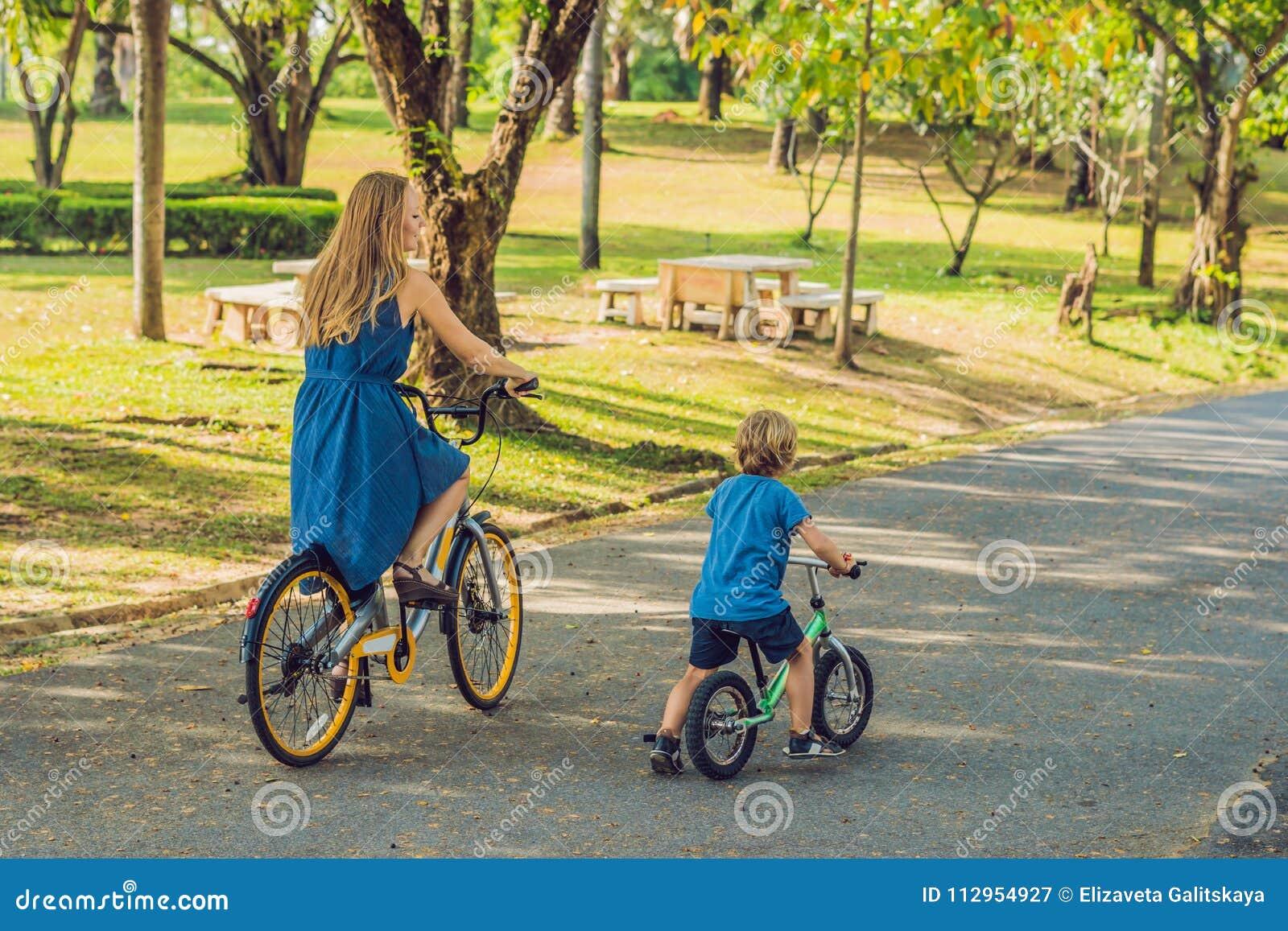 Den lyckliga familjen rider cyklar utomhus och att le Mamma på en cykel och en son på en balancebike