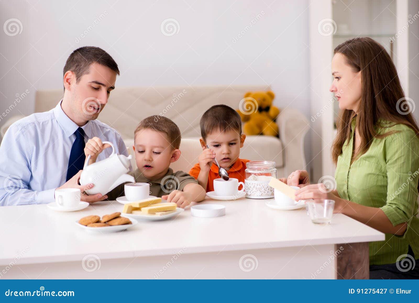 Den lyckliga familjen som har frukosten tillsammans hemma