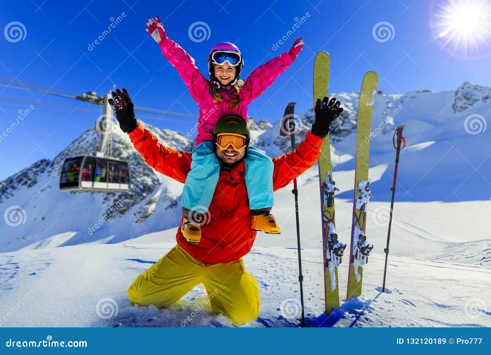 Den lyckliga familjen som tycker om vinter, semestrar i berg Skidar solen