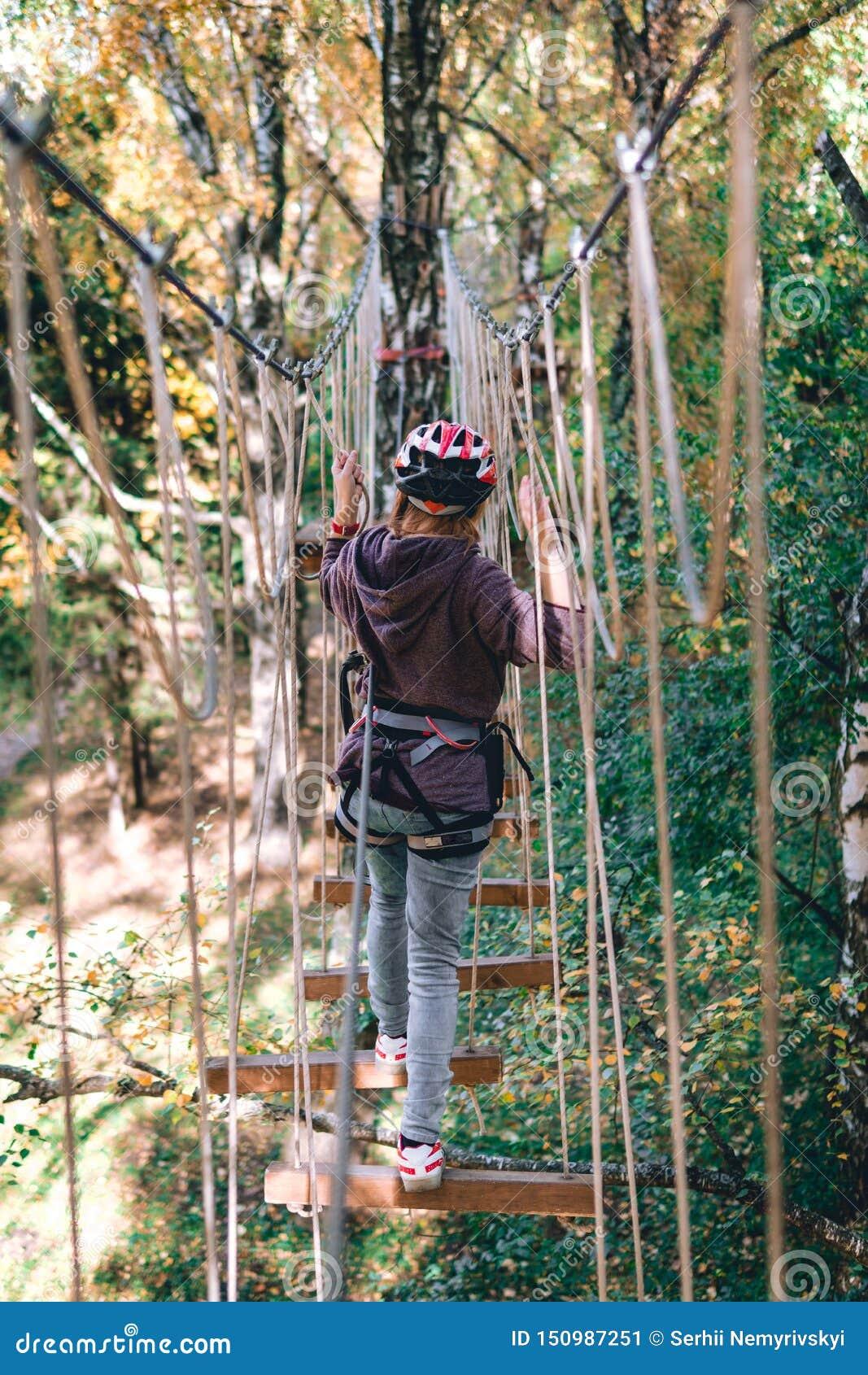 Den lyckliga flickan, kvinnor som klättrar kugghjulet i ett affärsföretag, parkerar kopplas in in vaggar klättringen på repvägen,