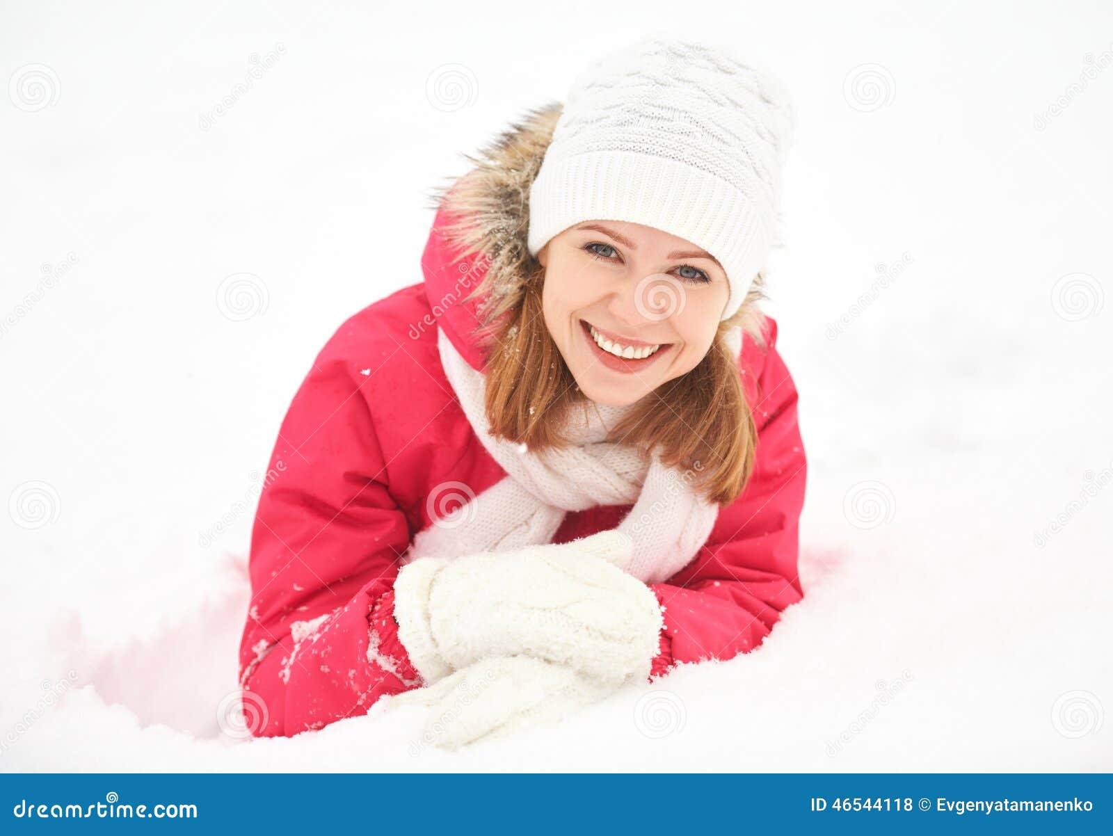 Den lyckliga flickan skrattar, medan ligga på den insnöade vintern utomhus